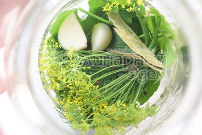 Листья смородины  и венчики укропа помыть и обсушить. Чеснок почистить. В стерилизованные банки укладываем на дно листья смородины, укроп, по 2 дольки чеснока, горошек, лавровый лист, гвоздику