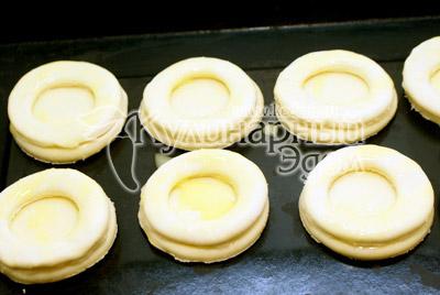 Переложить на противень большие кружки, на них уложить формочки от маленьких кружков. Смазать желтком и поставить в разогретую до 200 градусов С духовку и выпекать 10-12 минут