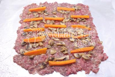 Фарш разровнять тонким слоем по небольшому кусочку фольги. Выложить грибы и брусочками порезанную морковь
