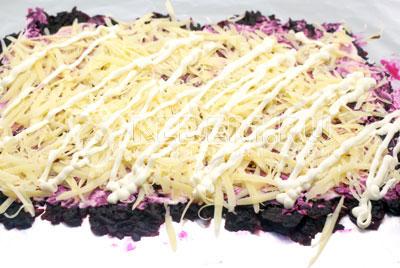 Вторым слоем выкладываем тертый сыр и смазываем майонезом