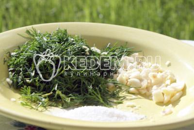 В миску нарезать укроп и нарубить чеснок, добавить соль и перемешать