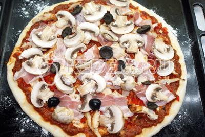 Бекон порвать руками, шампиньоны нарезать пластинками, маслины разрезать пополам и равномерно распределить по пицце