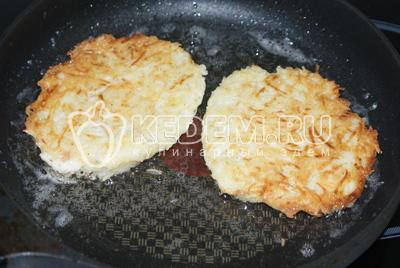 Формовать руками картофельные драники и обжарить их на растительном масле с двух сторон до золотистой корочки.