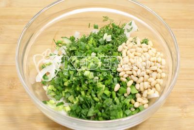 Добавить в миску с салатом мелко нашинкованный зеленый лук, зелень укропа  и кедровые орехи