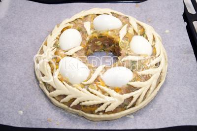 Из слоеного размороженного теста сделать декоративные элементы и уложить на фарш. Яйца отварить и остудить. Отварные яйца разрезать на половинки и утопить в фарше