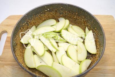Форму смазать сливочным маслом и посыпать сухарями. Выложить слой яблок на дно формы.
