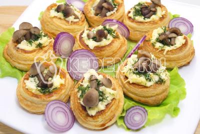 Разложить маринованные опята и выложить на блюдо с листьями салата и колечками красного лука.