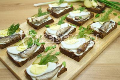 Выложить на каждый бутерброд шпроты и украсить веточками укропа. Посыпать мелко нашинкованным зеленым луком.