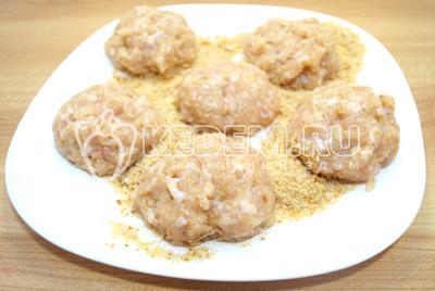 На блюдо высыпать панировочные сухари, разделить фарш на части.