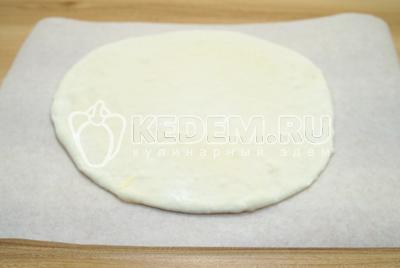 Разделить тесто на 2 части. Оду часть убрать про запас. Вторую раскатать в круг. Выложить на пергамент основу из теста.