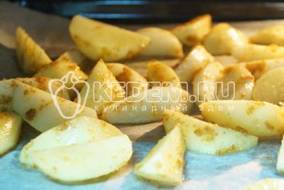 Поставить в разогретую до 200 градусов с духовку на 7-10 минут (зависит от размера ломтиков картофеля).