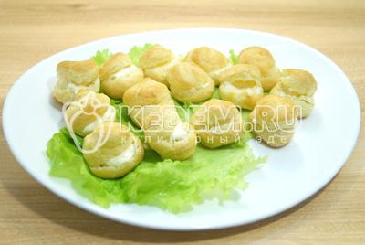Начинить каждую сливочным сыром и выложить на блюдо с листьями салата.