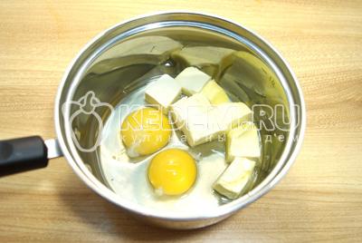 В сотейник разбить яйца и добавить сливочное масло.