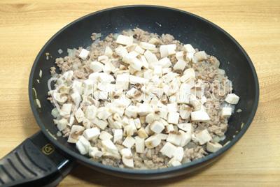 Добавить грибы с фарш и готовить еще 3-4 минуты.