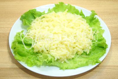 На блюдо выложить слой тертого  картофеля, немного посолить.