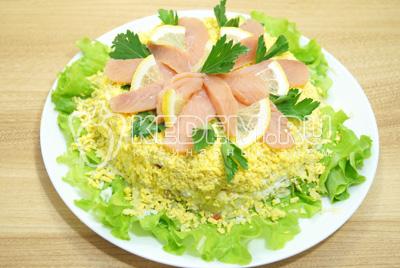 Сверху выложит вторую половину ломтиками нарезанной рыбы и украсить зеленью. Салат оставить пропитаться  в холодильнике.