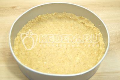 В разъемную форму выложить массу из печенья и хорошо разровнять. Сделать небольшие бортики. Поставить в холодильник на 20 минут.