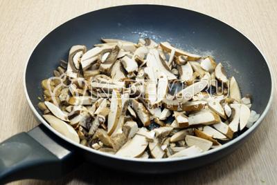 Нарезать соломкой грибы, лук мелко порубить, обжарить на сковороде с растительным маслом, 5 минут помешивая.