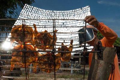 Тайский продавец уличной еды готовит курицу с помощью солнечных лучей