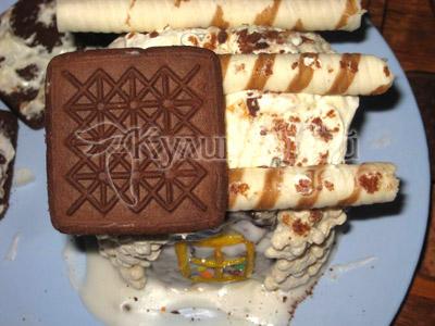 Торт «Сказочный домик» - 4 печенья, которые станут кровлей крыши, промазать сметаной и потом – тонким слоем творожной массы. Приклеить печенье к основе крыши.