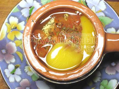 Накрыть сыр смесью помидоров и перца, в каждую из кокотниц влить по яйцу
