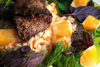 На широкое блюдо уложите горку риса, сверху поместите несколько кусочков печени, подножие «пирамиды» выложите травами и кусочками апельсина.