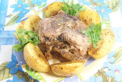 Выкладываем в середину блюда мясо, а по краям половинки картофеля, украшаем зеленью. - Запеченная свинина на косточке с картофелем .