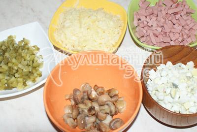 Грибы порезать, обжарить на подсолнечном масле 5-10 минут. Яйца отварить. Порезать кубиками колбасу, огурцы, яйца. Сыр натереть на терке.