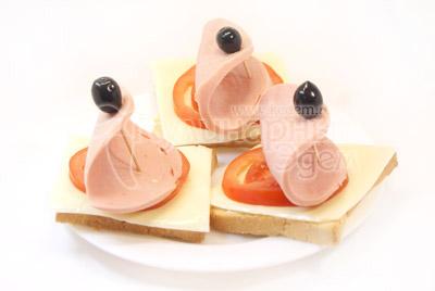 При помощи зубочистки и оливки закрепить кружок колбасы как парусник. - Бутерброды «Кораблики». Фото приготовления рецепта.