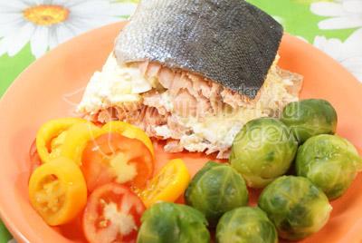 Выложить кусочек рыбы на блюдо, на гарнир выложить капусту и украсить дольками свежего помидора. - Слоёная рыбка. Фото приготовления рецепта.
