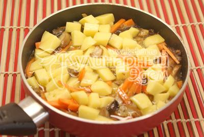 Добавить картофель кубиками. Перемешать, посолить. Добавить воды, закрыть крышкой и тушить до готовности картофеля