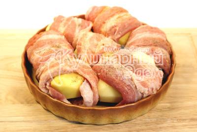 Картофель очистить и завернуть каждую картофелину в кусочек грудинки. Выложить в форму для запекания