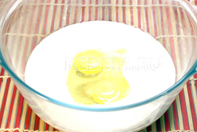 Отдельно, в большой миске, смешайте кефир, яйца (оставьте 1 желток), масло