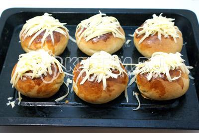 Горячие булочки посыпьте тертым сыром и поставьте в горячую выключенную духовку