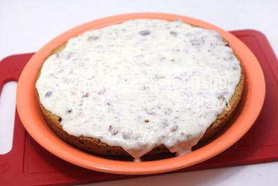 Выложить на блюдо нижнюю часть коржа и полить кремом