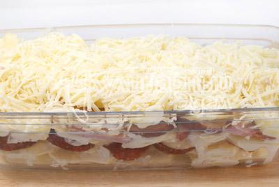 Последний слой картофеля, сверху слой небольших кусочков сливочного масла и всё посыпать тертым сыром