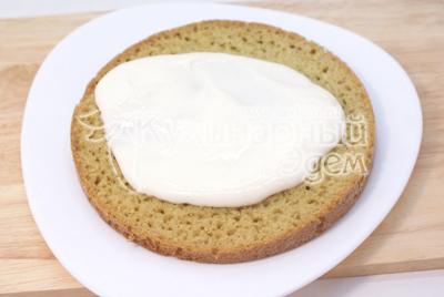 Нижнюю часть коржа переложить на блюдо и пропитать частью крема
