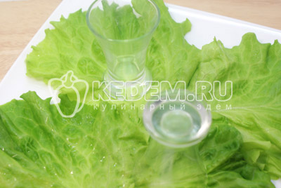 На тарелку уложить листья салата и поставить пару стаканов или стопочек для оформления