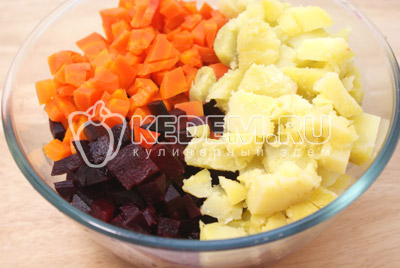 Свеклу, морковь и картофель заранее отварить, остудить и очистить. Смешать в миске кубиками порезанные: свеклу, картофель и морковь