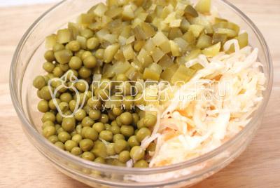 В другой миске смешать горошек, капусту и кубиками порезанные огурцы