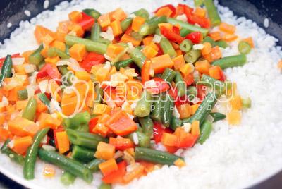 Добавить воды так, что бы прикрывало рис. Закрыть крышкой и готовить на среднем огне. После добавить еще воды, повторять пока рис не приготовиться. Добавьте овощи. Посолите