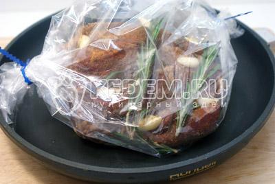 Выложить в пакет для запекания и добавить веточки розмарина. Завязать и сделать несколько проколов в пакете. - Свинина запеченная  с чесноком и розмарином. Фотография приготовление рецепта.