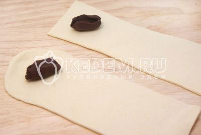 Раскатать полочки, каждую полоску еще затем разрезать на части длиной 5-7 см. На каждую полоску положить по кусочку шоколада