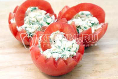 Срезать «крышечки» и вынуть мякоть. Нафаршировать помидоры. Из оставшихся крышечек вырезать дугообразные заготовки и вставить в помидоры