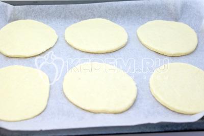 Раскатать в пласт и при помощи стакана вырезать лепешки. Противень застелить бумагой для выпечки ТМ РАКЛАН . Выложить лепешки на бумагу