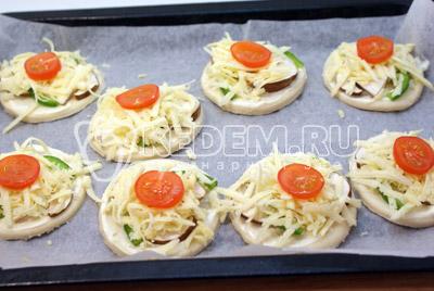 Посыпать тертым сыром. Уложить сверху ломтики помидорок черри