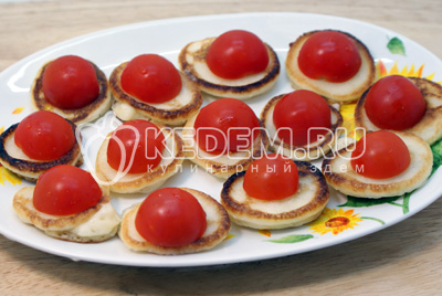 Выложить в один слой оладьи и сверху уложить половинки помидорок черри