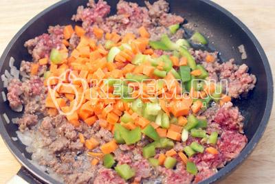 Добавить кубиками порезанную морковь и перец. Обжаривать еще 2-3 минуты