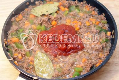 Добавить томатную пасту, 2 листика лаврового листа, чеснок, сахар и соль. Готовить на медленном огне до готовности 10-12 минут
