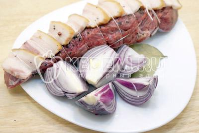 Мясо натереть солью и перцем. Сверху уложить ломтики корейки. Перевязать кулинарной нитью. Лук крупно нарезать.